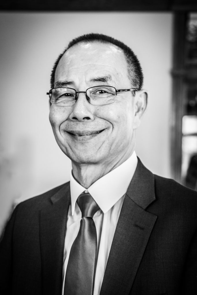 A black and white portrait of Chinese man wearing glasses in a suit. His name is Roger Hon Chung Chan.