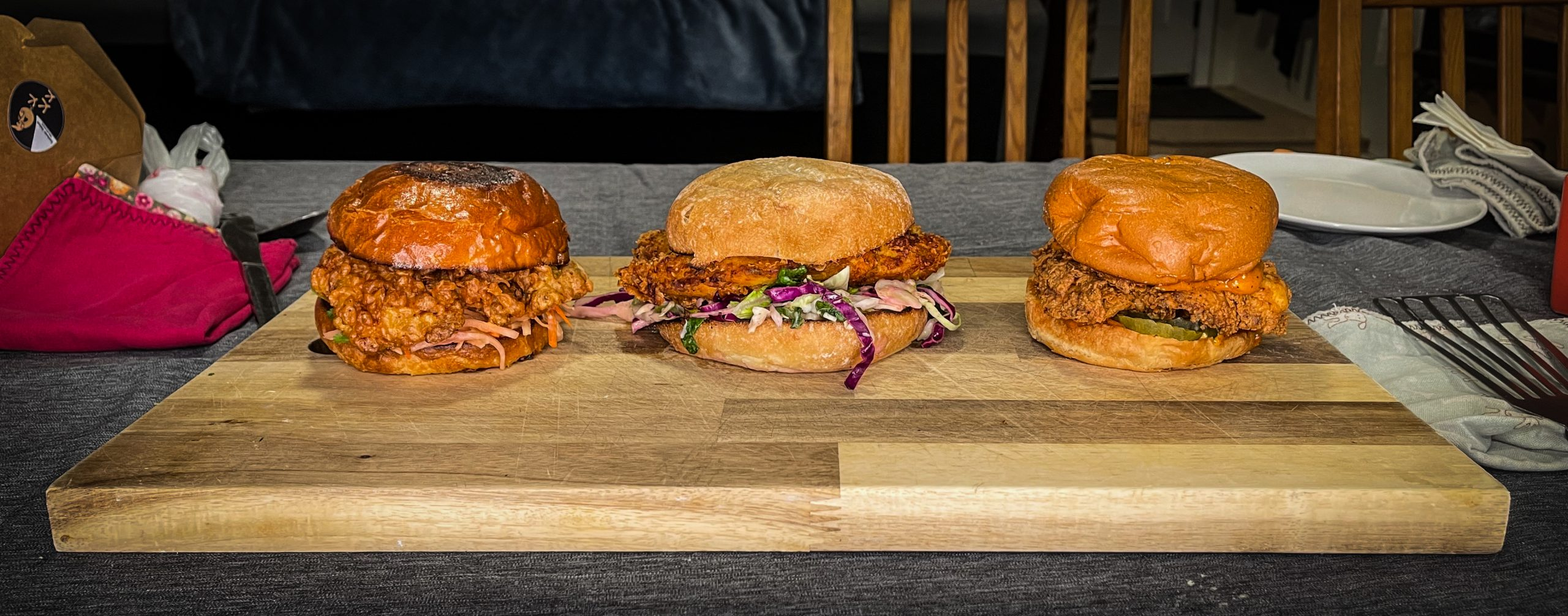 Three fried chicken sandwiches on a cutting board.