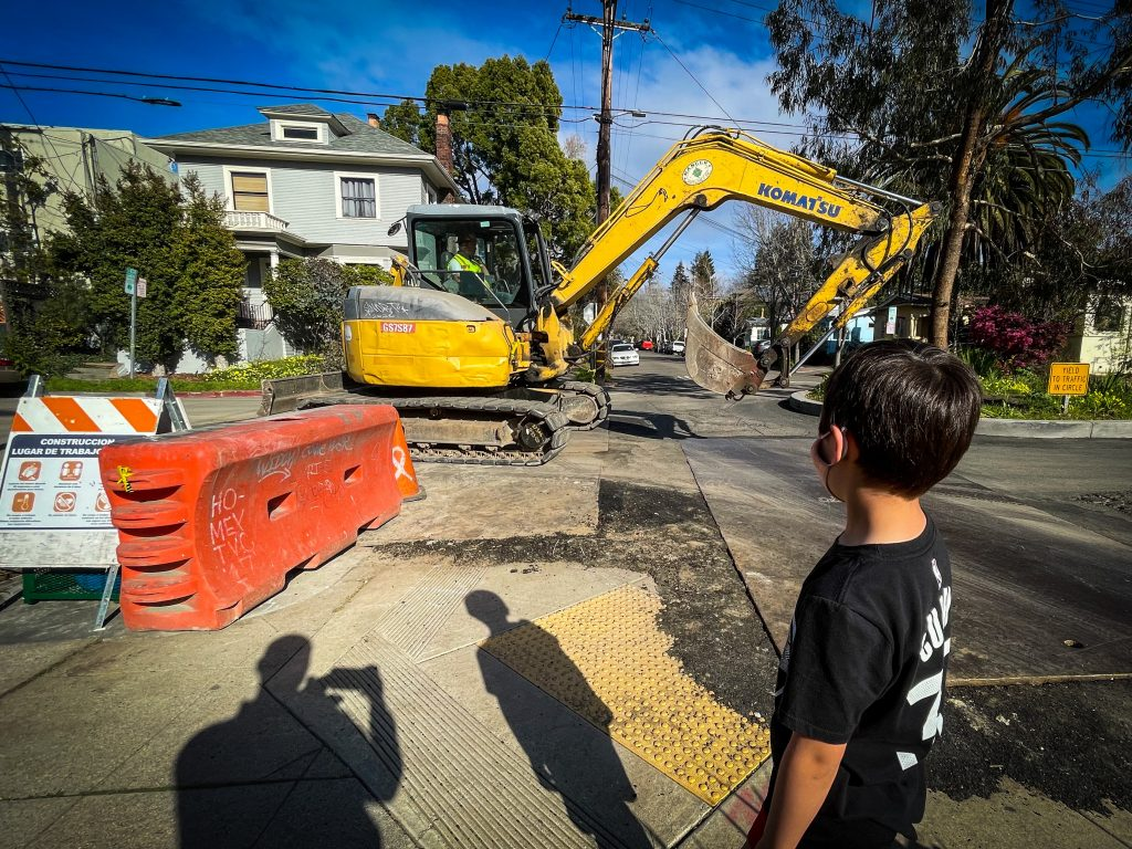 A yellow back hoe  is in front of a small boy who is watching      It roll by.