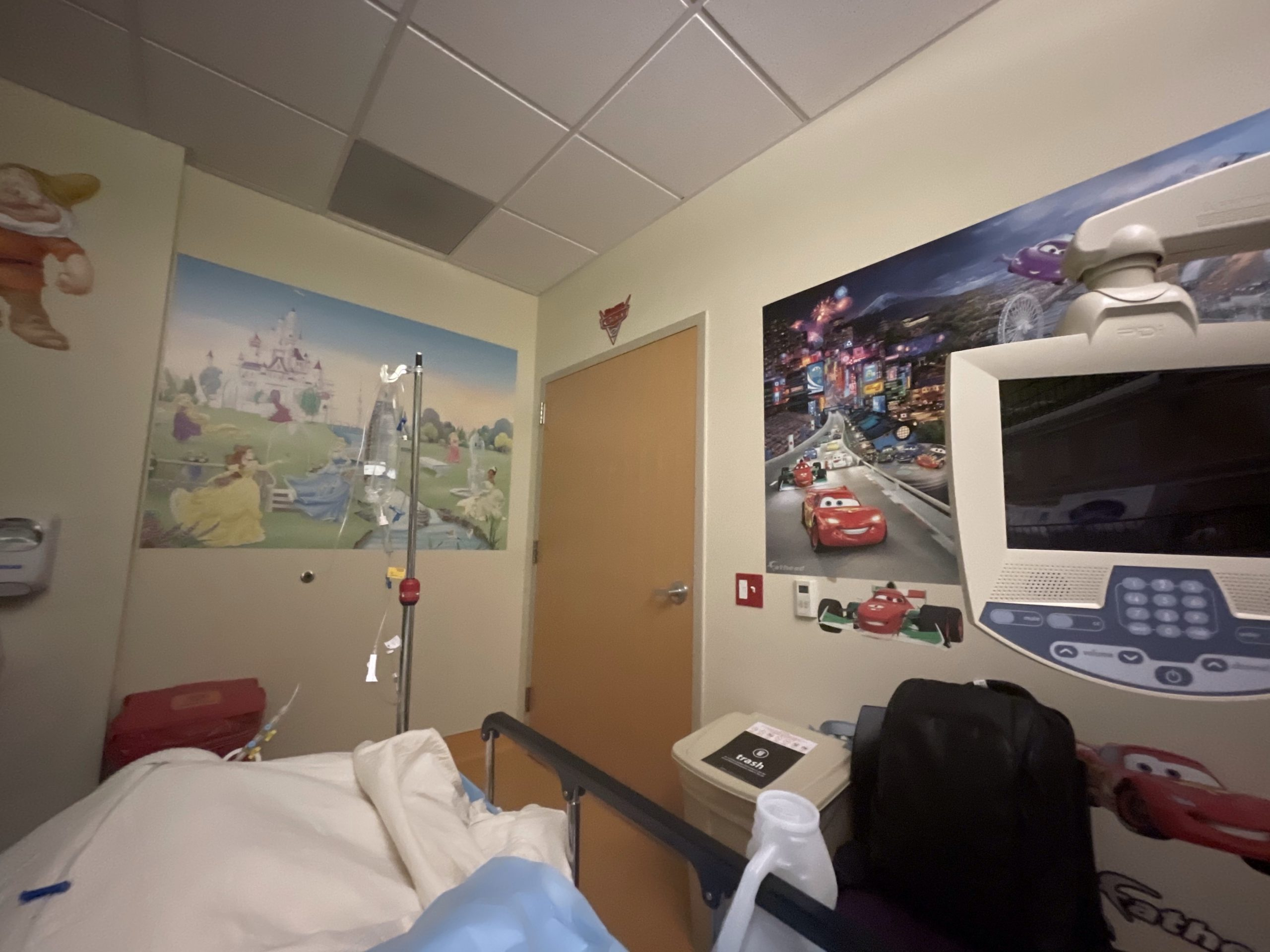 Wide angle photo of hospital room. There is a bed, IV and tv screen in the foreground and posters of animated characters on the walls.